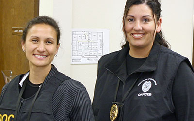 two female community corrections officers smiling at the camera