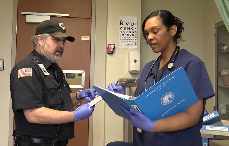 Correctional Officer and Nurse working together sharing notes